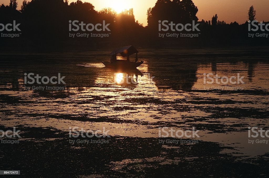 Lake at Sunset and Boat Silhouette royalty-free stock photo