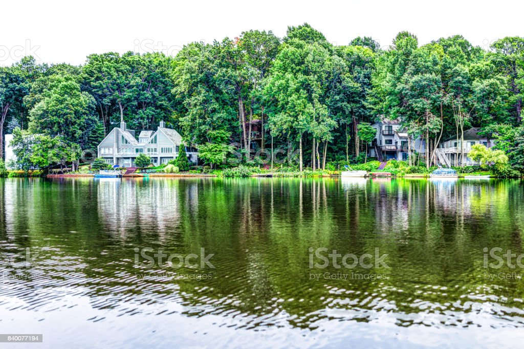 Audubon lago com beira-mar à beira do Lago casas em Reston, Virginia, com reflexão de folhagem de verão verde nas árvores foto royalty-free