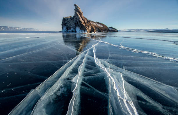 Lake Baikal is a frosty winter day. Largest fresh water lake. Lake Baikal is covered with ice and snow, strong cold and frost, thick clear blue ice. Icicles hang from the rocks. Amazing place heritage stock photo