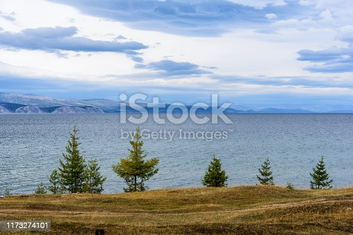 Lake Baikal, tree and mountains of Siberia with beautiful sky and clouds in autumn peaceful day, Russia Oklhon island