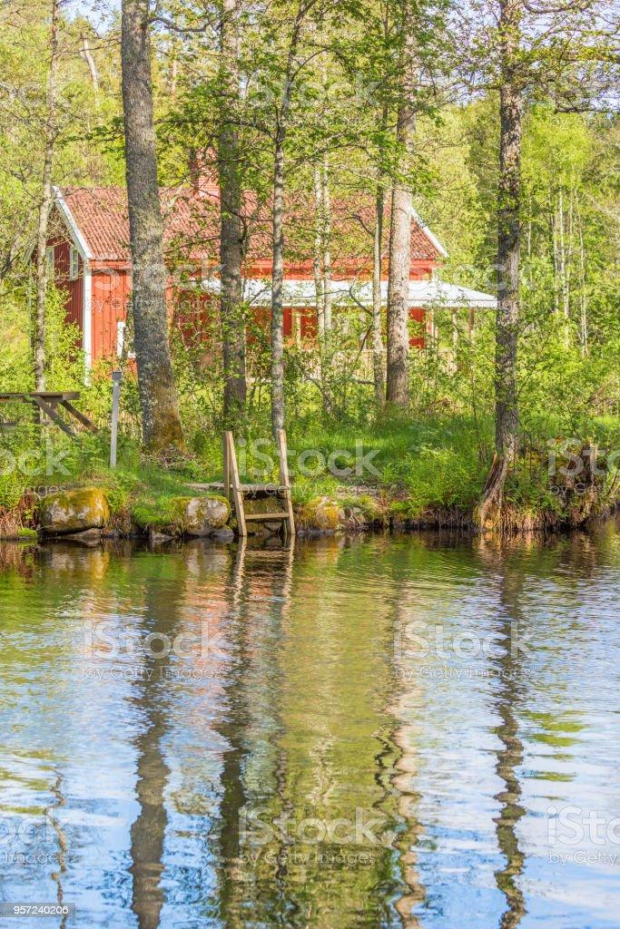 Strandbad mit einem roten Häuschen im Wald – Foto