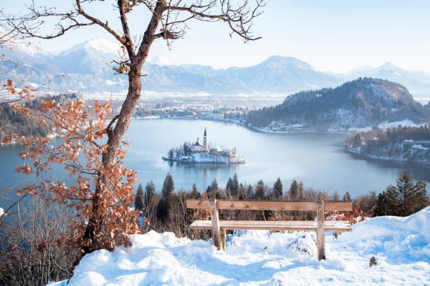 bleder see mit holzbank im winter, slowenien - kleinstadt ansicht stock-fotos und bilder