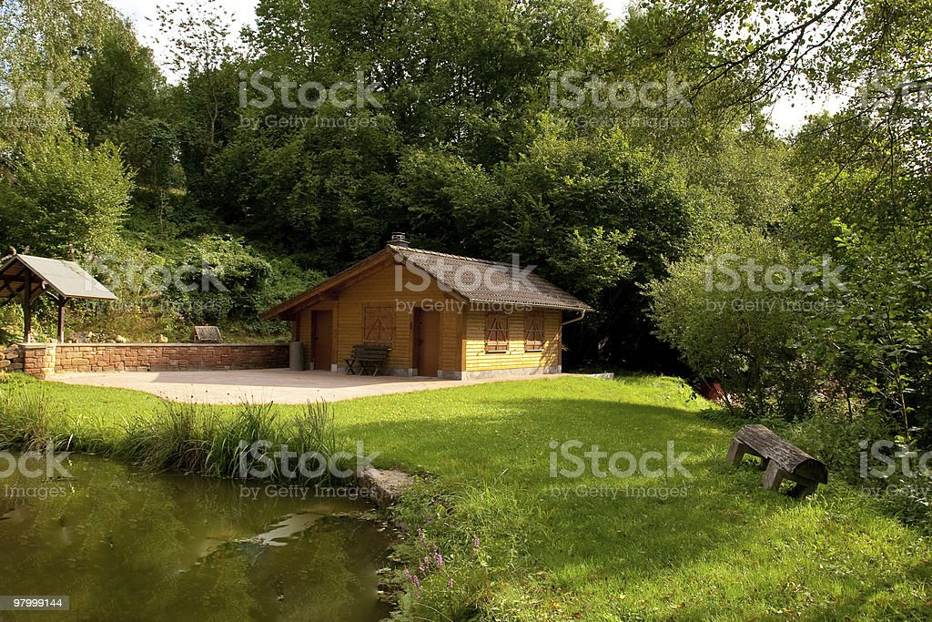 lake cabin sport fishing pond green grass trees water bench royalty-free stock photo