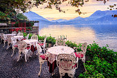 Tables in a small cafe at the waterfront of Lake Como, Italy, with panorama of the Alps Mountains in background on sunset