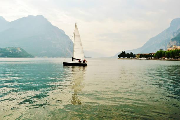 Lake Como at Lecco with sailboat navigating from the city. stock photo