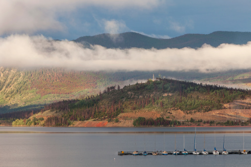 Summer sunrise at Lake Dillon in Colorado Rocky Mountains with sailboats and visible forest damage by pine beetle