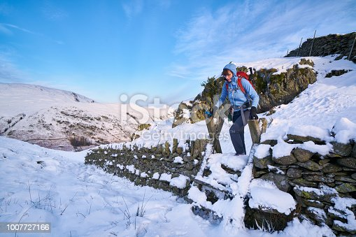 Hiker crossing a stile over a stone wall at Hartsop Above How in the English Lake District.