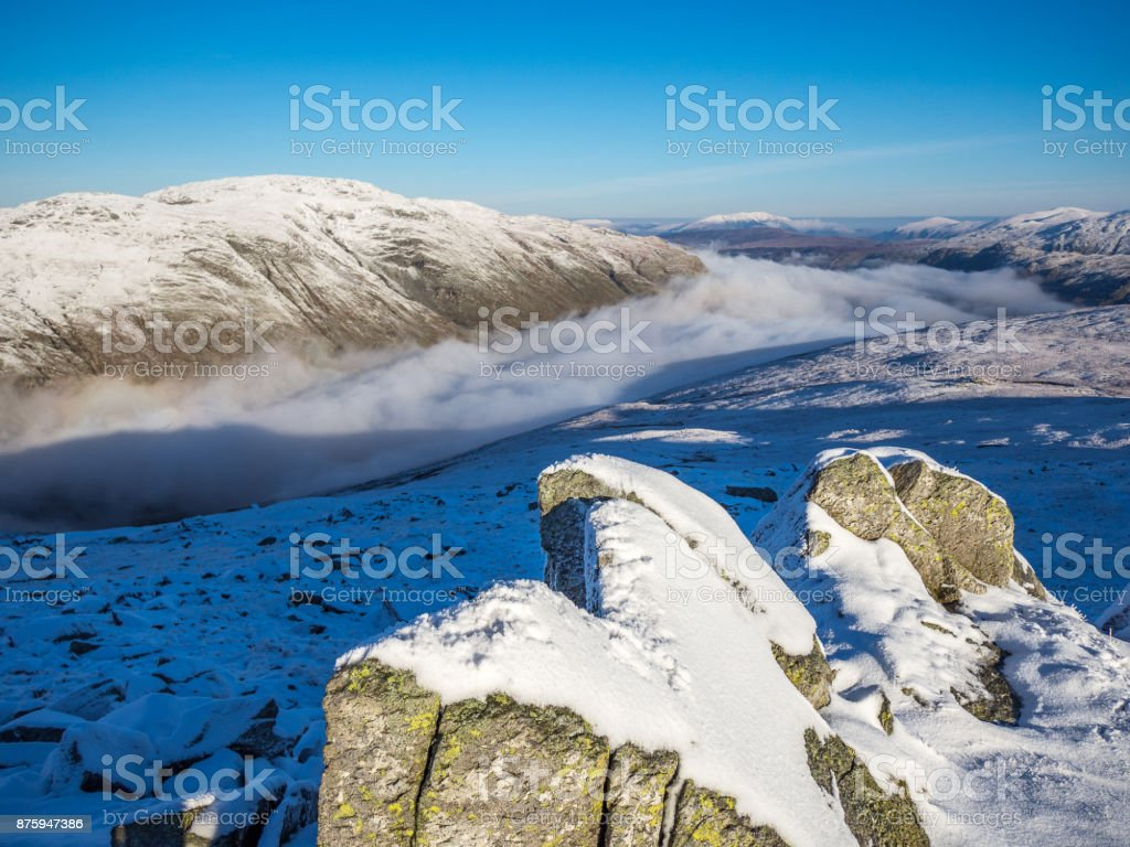 Lake District Temperature Inversion clouds in valley with snow covered peaks stock photo