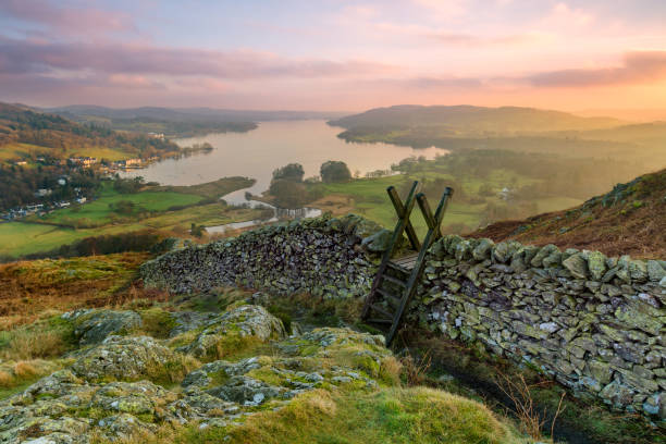 Lake District Winter Sunset. Beautiful sunset over Windermere in the Lake District with a stile and stone wall in the foreground. cumbria stock pictures, royalty-free photos & images