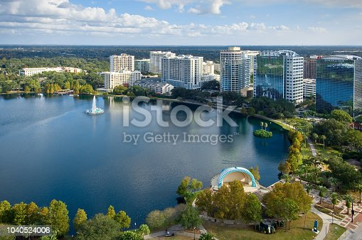 A fountain and two lush palm trees in the middle of Lake Eola. Cityscape surrounding the lake emphasizing the cohabitation of man and nature in Florida. A large walkway for tourists and locals to walk around the lake, and a background of trees, clouds, and sky encompass the rest of the shot.