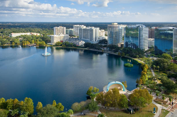 lake eola surrounded by buildings and trees - orlando florida photos stock photos and pictures