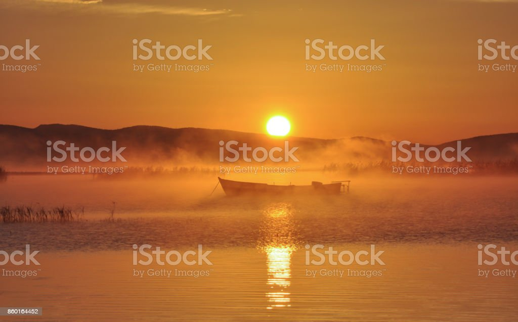 lake evaporation and fishing boat stock photo