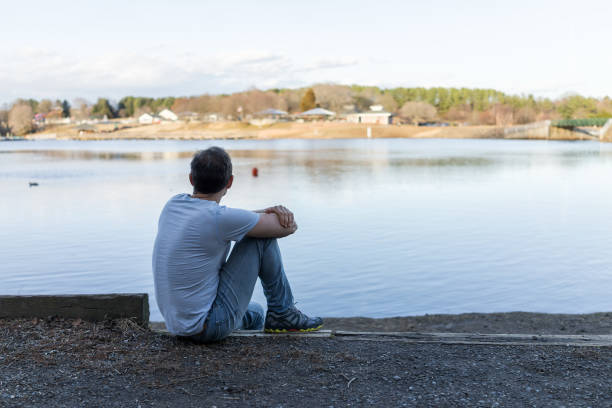 17 Man Sitting By Calm Blue Lake In Depressed Lonely Contemplation Stock  Photos, Pictures & Royalty-Free Images - iStock