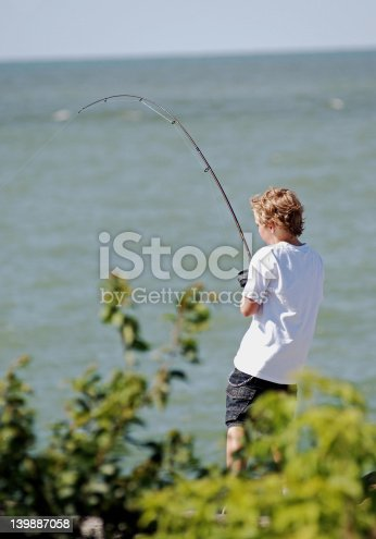 A little boy reeling in a fish from the lake.