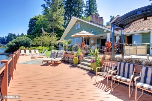 Great large brown new deck with lake front green house.