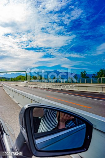 Lake Geneva in Switzerland with a motorway in the foreground viewed through the side window of a car on the motorway near Lake Geneva.
