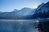Lake Hallstatt with the sun about to disappear behind the mountain range of Dachsteinmassiv. Two swans are in the cold lake while the last sunrays hit the water and reflect from the surface against a mountian backdrop.