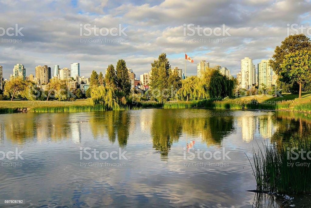 lake in a park with city skyline in the background stock photo