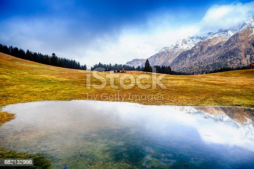 Small lake in the Italian Dolomites. Beautiful mountain landscape with reflection in the water, clouds and snowy peaks.