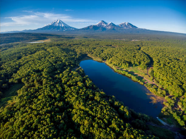Lake in forest and volcano mountainscape at horizon aerial Lake in forest and volcanic mountain scape at horizon aerial kamchatka peninsula stock pictures, royalty-free photos & images