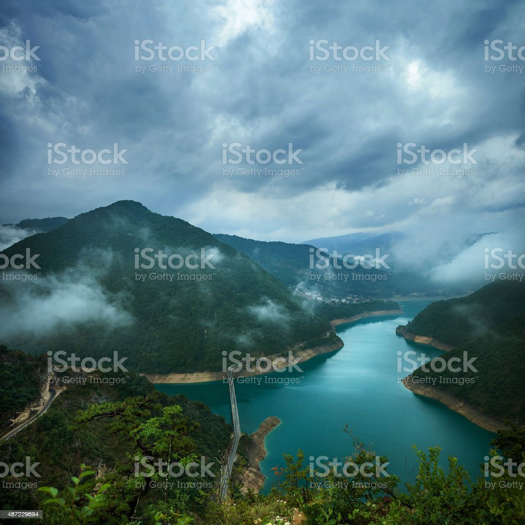 Lake in the mountains under the stormy sky stock photo