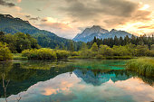 Scenic view of mountains and green forest reflecting in shiny lake of Zelenci Springs nature reserve,Upper Carniola,Slovenia
