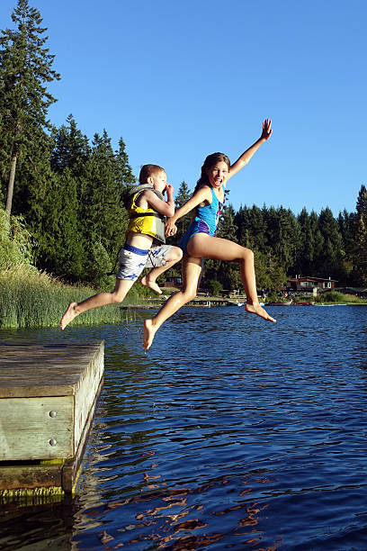 lake jumping - st. mary lake stock pictures, royalty-free photos & images