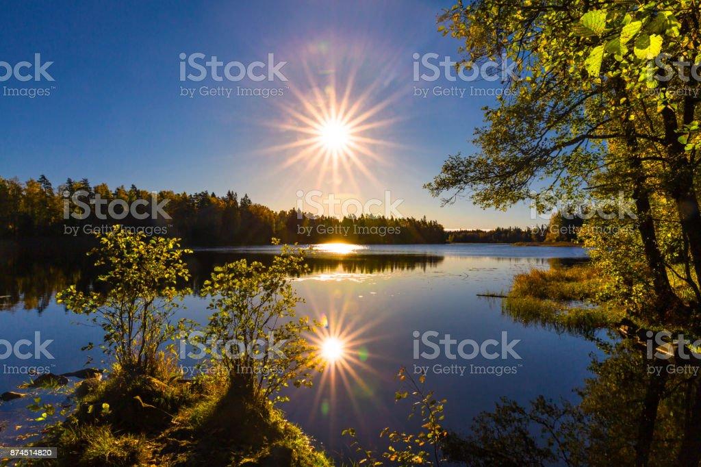 Sjön kysst av starshaped solen bildbanksfoto