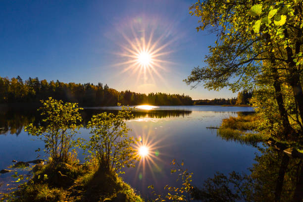 Lake kissed by starshaped sun stock photo