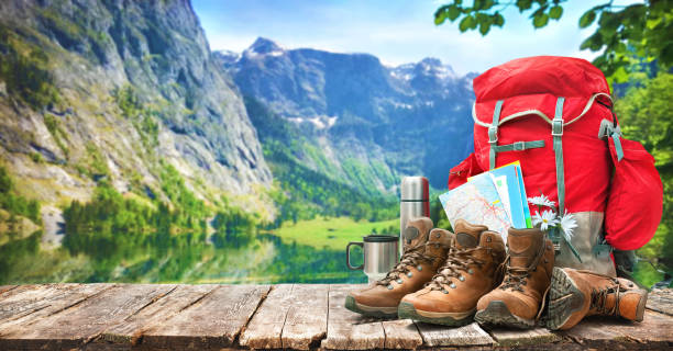 lake landscape with big backpack and trekking boots - camping stock photos and pictures