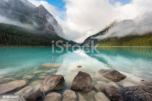 Wide angle view of Lake Louise at sunrise with a rainbow in Banff National Park, Alberta, Canada