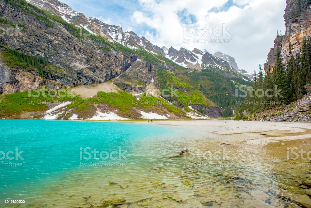 Lake Louise landscape end of lake with rock and sand beach foreshore with vertical mountains around the vivid blue lake water stock photo