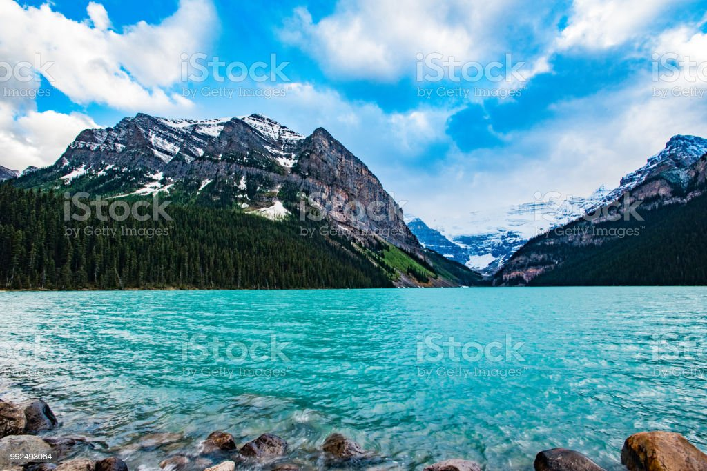 Lake Louise looking across the lake at mountains with rocky lake shore in the foreground stock photo