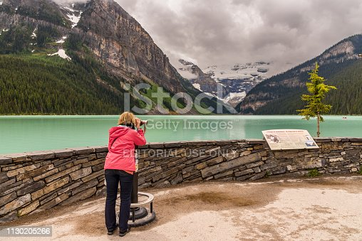 Lake Louise, Alberta / Canada - 06/19/2015 Lake Louise tourist viewing mountains with a cloudy sky in Canada
