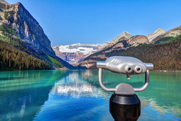Lake Louise With Mount Victoria Glacier in Banff National Park Focus on a tower viewer or binoculars at Lake Louise in Banff National Park with its glacier-fed turquoise lakes and Mount Victoria Glacier in the background. Visitors paddling red canoes in the distance. mt victoria canadian rockies stock pictures, royalty-free photos & images