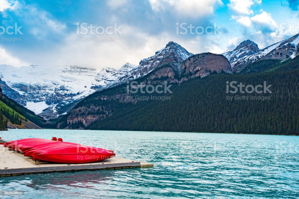 Lake louise with red canoes in the foreground and mountains in background stock photo