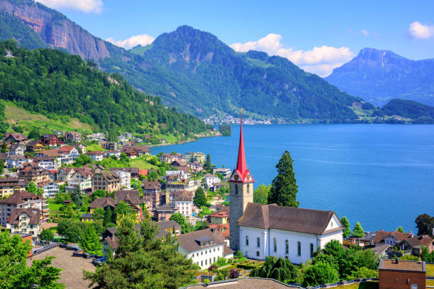 Lake Lucerne and Alps mountains by Weggis, Switzerland Little swiss town with gothic church on Lake Lucerne and Alps mountain, Switzerland zug stock pictures, royalty-free photos & images
