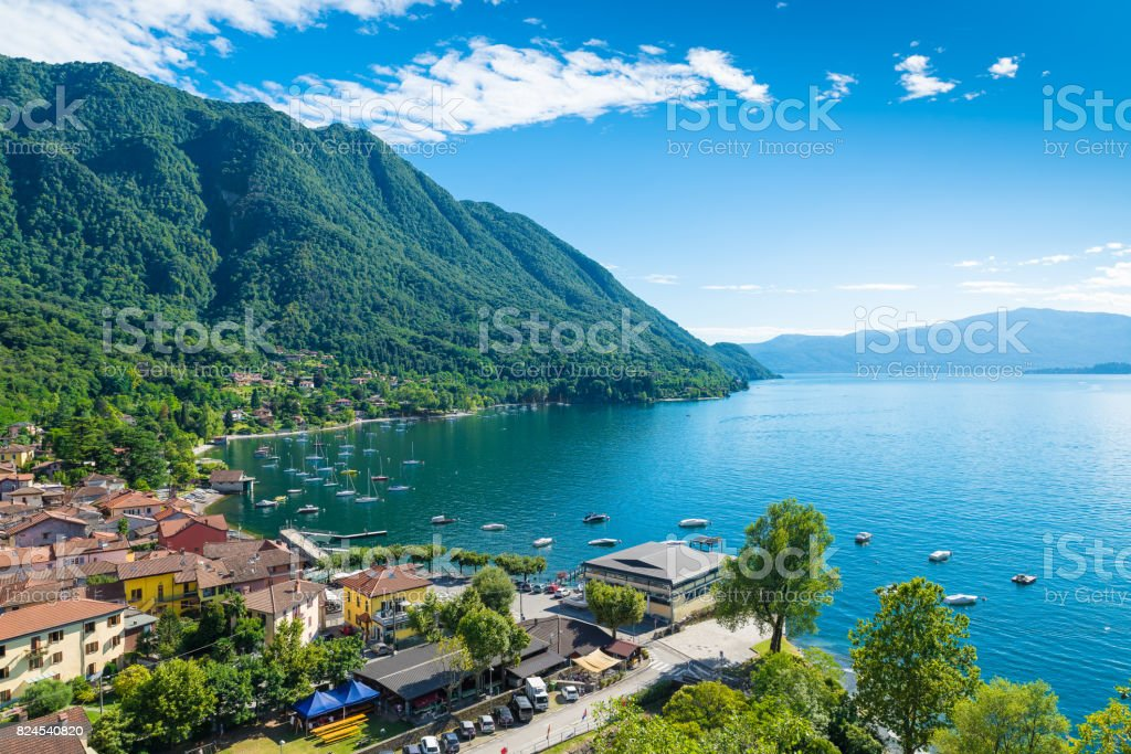 Lake Maggiore, Verbano, Caldè, northern Italy. One of the most charming corners of the lake Maggiore on a beautiful summer day. Aerial view of the small town, hamlet of Castelveccana, and of the small harbor stock photo