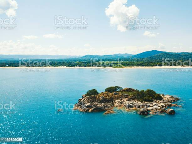 Photo of lake malawi with tiny island in the