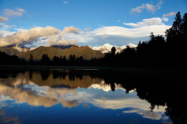 Lake Matheson New Zealand Lake Matheson on New Zealand's South Island, with the Southern Alps reflected in its mirror-like surface. lenticular cloud stock pictures, royalty-free photos & images