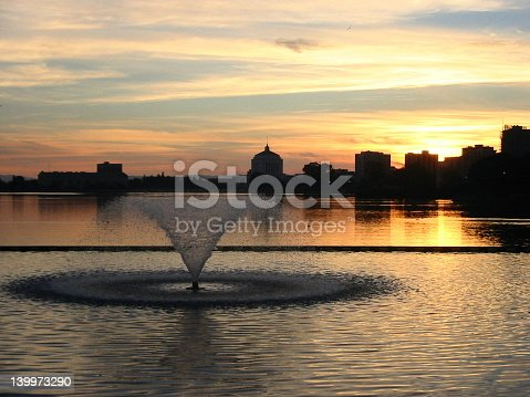 Sun setting over Oakland California's Lake Merritt, with Alameda Superior Court in the background.