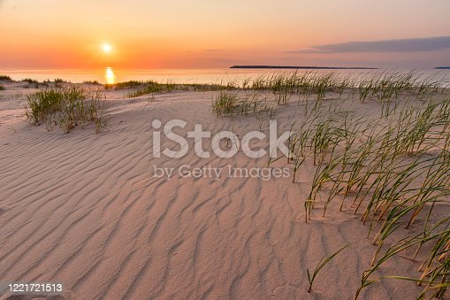 Sun sets o the on the horizon over Lake Huron Michigan just past the grass, sand and dune of Sleeping Bear National Lake Shore.  A composition taken from the sand dunes on Michigan's coast above the lake.