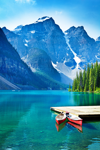 Lake Moraine in the Banff National Park of Canada, with its emerald water and mountain range of the Canadian Rockies. Red rental canoes moored against the dock with the dramatic natural scenic mountain lake in the background. Photographed in vertical format.