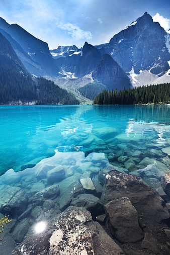 Lake Moraine in the Banff National Park, Alberta, Canada, features clear emerald water and snow-capped peaks of the Canadian Rockies mountain range. The scenic landscape is a famous place and a favorite tourist travel destination for North American great outdoors nature vacations. Vertical format with copy space and no people.