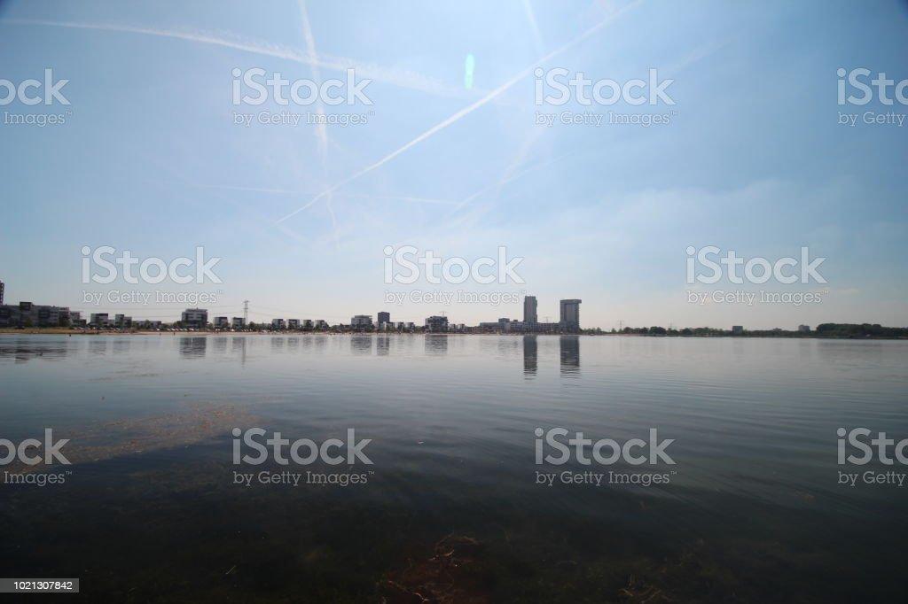 Lake genaamd Zevenhuizerplas in Zevenhuizen met zon op het water en de skyline van Nesselande strand en district in Rotterdam foto