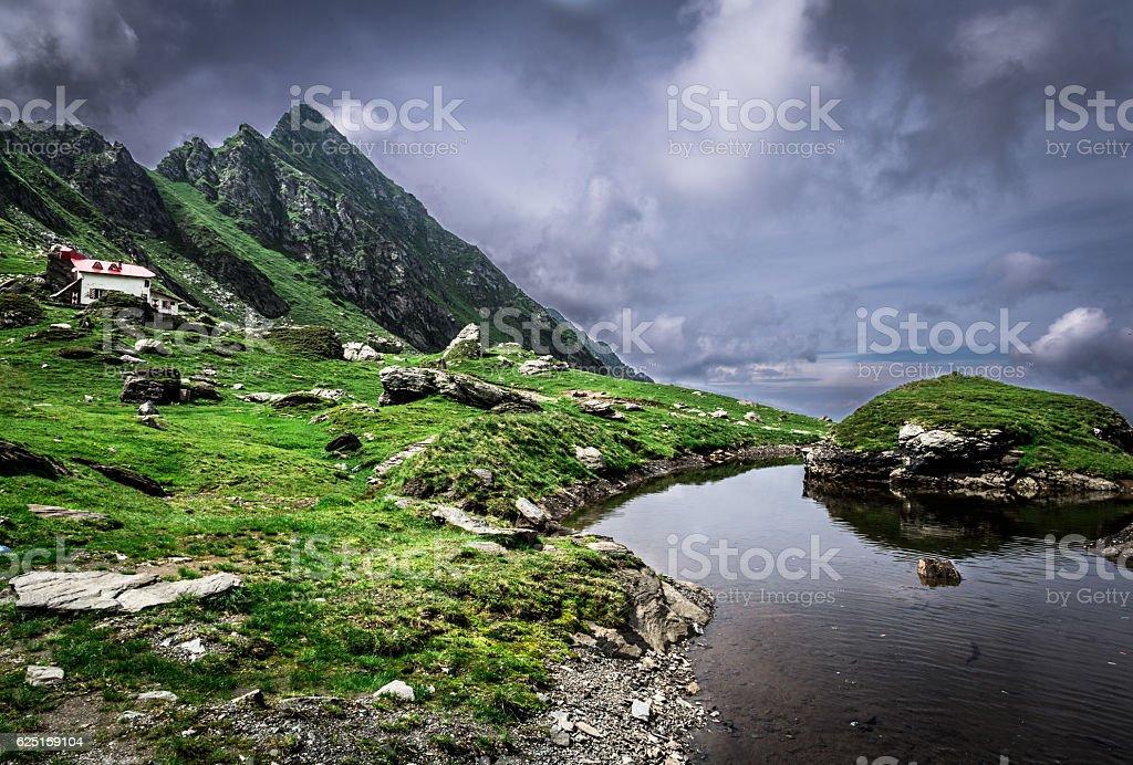 Lake, old house and mountains on Transfagarasan road, Transylvania, Romania stock photo