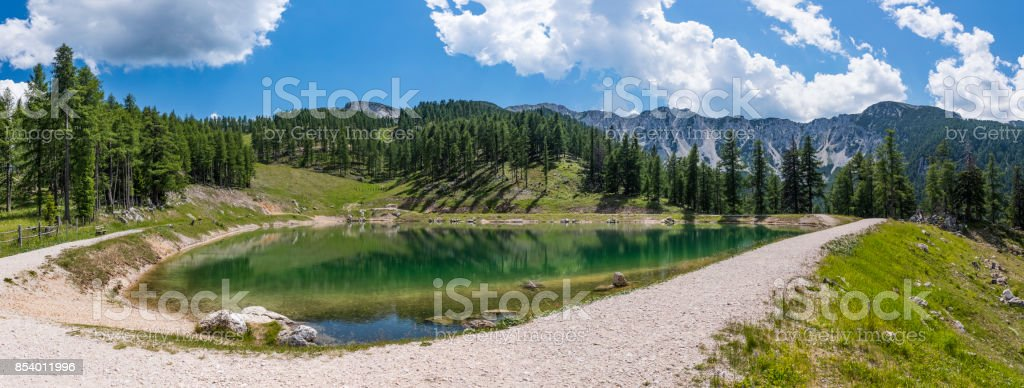 Lake on mountain Petzen with forrest and mountain Hochpetzen in the background stock photo