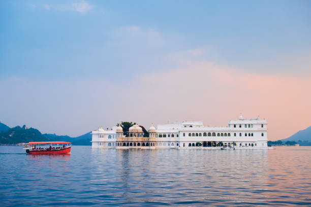 Lake Palace palace on Lake Pichola in twilight, Udaipur, Rajasthan, India Romantic luxury India travel tourism - tourist boat in front of Lake Palace (Jag Niwas) complex on Lake Pichola on sunset with dramatic sky, Udaipur, Rajasthan, India lake palace stock pictures, royalty-free photos & images