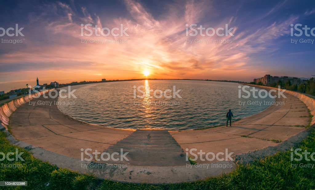 Lake panorama at sunset with a fisherman with dramatic clouds stock photo