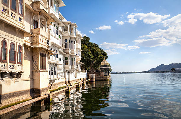 Lake Pichola in India Lake Pichola with residential houses at cloudy sky in Udaipur, Rajasthan, India lake pichola stock pictures, royalty-free photos & images